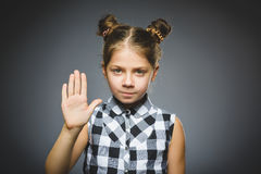 Girl shows the stop arm isolated on gray background. Portrait of angry girl with hand up yelling isolated on gray background. Negative human emotion, facial stock photos