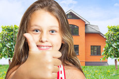 Girl shows thumb on red house Royalty Free Stock Image