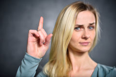 Girl shows up an index finger, expressing a sign of attention.  Royalty Free Stock Photo