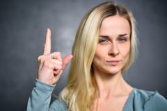 Girl shows up an index finger, expressing a sign of attention.  Stock Photos