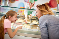 Girl shows what taste of ice cream wants Stock Photography