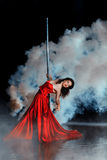 Girl shrouded in smoke dancing around a pole dance. Stock Photos