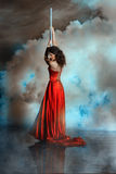 Girl shrouded in smoke holding on to pole dance. Royalty Free Stock Photos