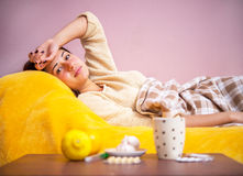 Girl sick in bed under the covers Stock Photography