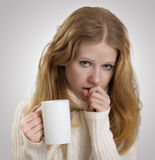 Girl sick with the flu coughs, a mug of tea Stock Photography