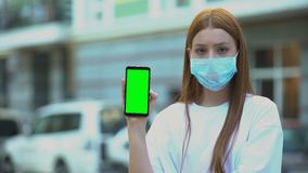 Girl in sick mask holding green screen phone, appointment with doctor online