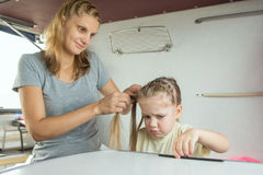 The girl is sick mother braids her pigtails, on a cot in a train Royalty Free Stock Image