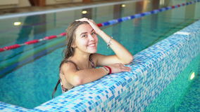 Girl at the side of the pool. Portrait of a girl at the side of the indoor pool stock video footage