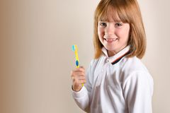 Girl on side showing tooth brush on isolated brown. Smiling girl on side showing tooth brush with toothpaste on brown background isolated. Horizontal composition royalty free stock photo