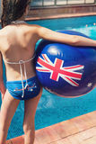 Girl on the side of a swimming pool with an Australian flag ball Stock Photos