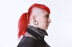 Girl with sidecut piercings and tattoos. Side view of young woman with sidecut, facial piercings and tattoos royalty free stock photography