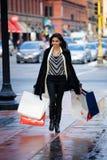 Girl on sidewalk with bags Stock Image