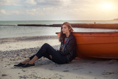 A girl sideways near a red boat on the beach by the sea Stock Photo