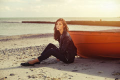 A girl sideways near a red boat on the beach by the sea. A girl sideways sitting near a red boat on the beach by the sea with beautiful sunset on the background Stock Photography