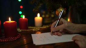 A girl signs Christmas greeting cards on a background of a Christmas tree, colored lights and candles