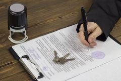 The girl signs a contract for the purchase of real estate, on the table lies the contract, the seal and the keys to the apartment stock photography
