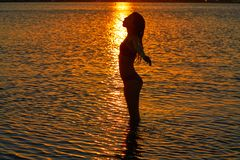 Girl silhouette at beach sunset open arms royalty free stock photo