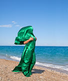 Girl silhouette in green tissue on the sea beach Stock Image