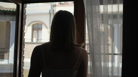 Girl silhouette opens window against neighbour house. Girl silhouette opens window and admires refreshing morning air against neighbour house at sunlight stock video