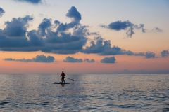 Paddle board. A girl silhouette on the paddle board, cloudy sunset sky background stock image