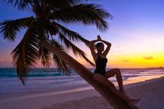 Girl silhouette palm tree Caribbean sunset. Girl silhouette on palm tree Caribbean sunset beach of Riviera Maya Mexico Stock Photo