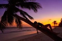 Girl silhouette palm tree Caribbean sunset. Girl silhouette on palm tree Caribbean sunset beach of Riviera Maya Mexico Royalty Free Stock Photo