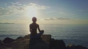 Girl Silhouette Sits in Pose under Bright Sun Path. Girl silhouette sits in yoga position ArdhaPadmasana on rocks under bright sun path on ocean water surface stock video