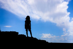Girl in silhouette stands on hill. Stock Photos
