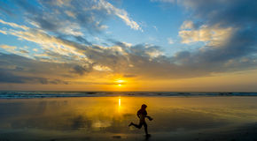 Girl silhouette and sunrise. Silhouette of children running with sunrise background Royalty Free Stock Photography