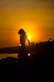 Girl silhouette on sunset beach background Stock Photos