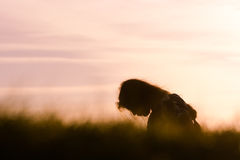 Girl silhouetted in profile in front of purple sunset Royalty Free Stock Photography