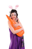 Girl in a silk dress, with rabbit ears and carrot Royalty Free Stock Photos