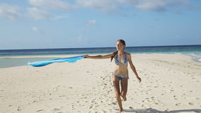 Girl with silk fabric walking along the beach stock footage