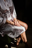 A girl in a silk robe sitting on a chair and crosses her hands on her knees Stock Photo
