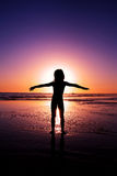 Silhouette of a girl with open arms in the ocean Royalty Free Stock Image