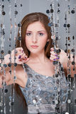 Girl in silver dress. Girl with purple nails in silver dress holding beads stock image