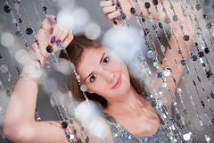 Girl in silver dress holding beads. Girl with purple nails in silver dress holding beads stock photo