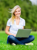 Girl with silver laptop sitting on the grass Royalty Free Stock Images