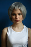 Girl in silver wig and white singlet posing . Close up. Blue background Stock Photos
