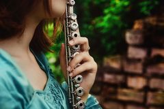 Girl with a silvery flute. The girl is dressed in a blue dress royalty free stock photography