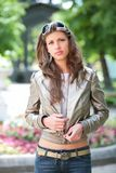Girl in silvery jacket. Beautiful girl in silvery jacket and sunglasses in park Stock Images