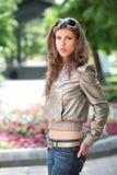 Girl in silvery jacket. Portrait of the dark-haired girl in silvery jacket royalty free stock photography