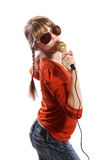Girl sing. Girl with big sunglasses sings into a microphone on a white background Royalty Free Stock Images