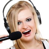 Girl singer musician with headphones singing to mi. Emotional blonde girl singer performer musician singing a song to microphone isolated on white. young royalty free stock photo