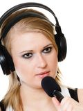 Girl singer musician with headphones singing to microphone Stock Images