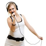 Girl singer musician with headphones singing to microphone Stock Photography