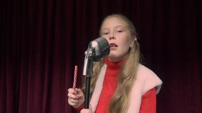 Girl singer singing song front retro microphone on dark stage while performance. Young girl singer performing and singing song dark stage. Musical Christmas royalty free stock photo