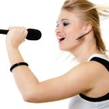 Girl singer singing to microphone  on white. Royalty Free Stock Images