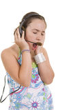 Girl singing. A young girl listening music and singing Stock Photography