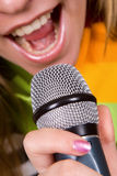 Girl Singing In Microphone Stock Image